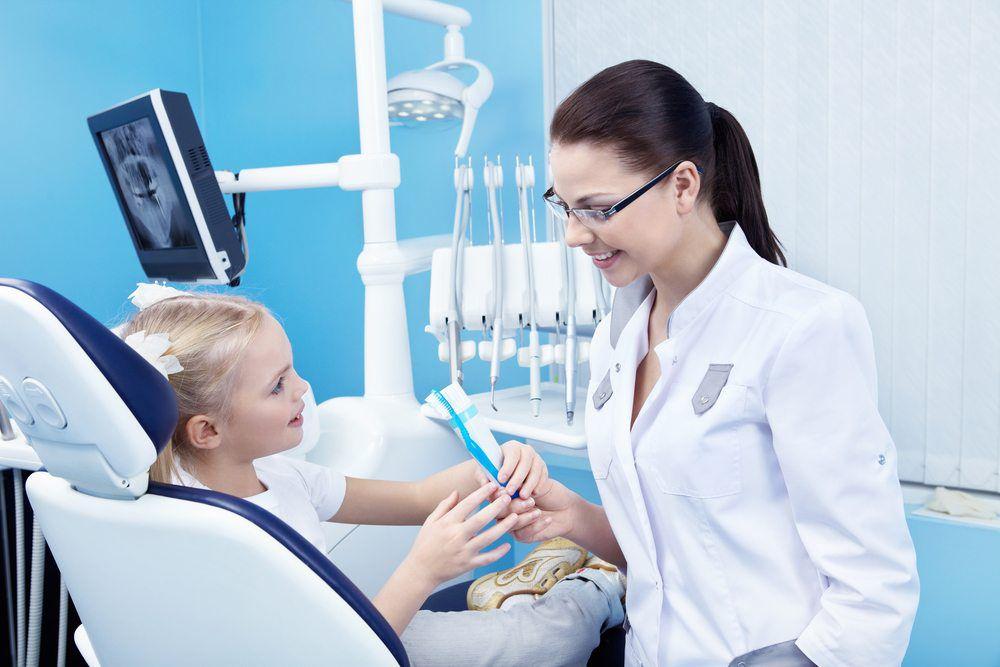 A Female Dentist explaining a kid to brushing teeth procedure  05
